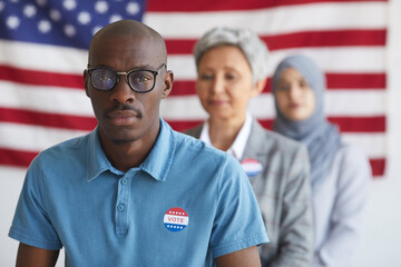 Multi-ethnic group of people at polling station on election day, focus on African-American man with I VOTED sticker looking at camera, copy space