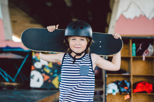 Portrait of handsome caucasian boy athlete skateboarder in protective helmet with skateboard in hands looking at camera on background of skate park. A child and an active hobby, sports and health