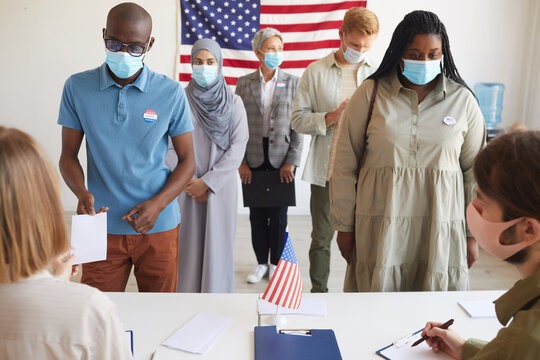 Front view at multi-ethnic group of people standing in row and wearing masks at polling station on election day, focus on two African-American people registering for voting