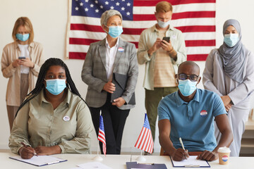 Multi-ethnic group of people standing in row and wearing masks at polling station on election day, focus on African-American couple looking at camera while registering for voting