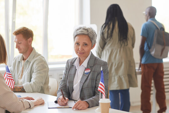 Portrait of modern mature woman registering voters while working at desk on election day, copy space
