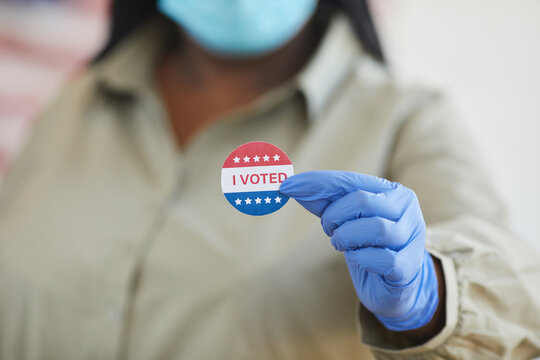 Close up of unrecognizable African-American woman holding I VOTED sticker while standing at polling station on post-pandemic election day, copy space