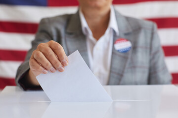 Close up of mature woman putting vote bulletin in ballot box while standing against American flag on election day, copy space