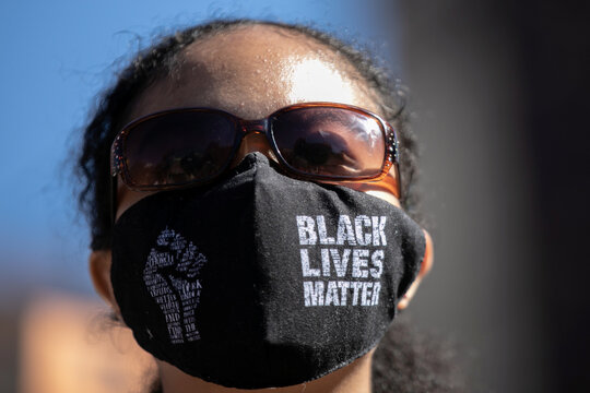 """A woman wears a face mask with written """"Black Lives Matter"""" on it during a march demanding Donald Trump and Mike Pence leave office on Union Square in the Manhattan borough of New York City"""