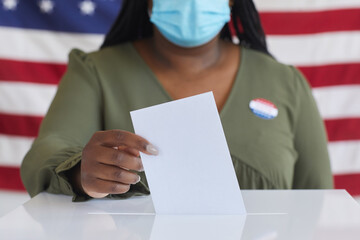 Close up of African-American woman wearing mask putting vote bulletin in ballot box and looking at camera while standing against American flag on election day, copy space