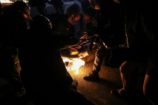 Protesters help a man who caught fire from a Molotov cocktail thrown during a confrontation with Portland police in Portland, Oregon