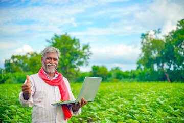Indian farmer using a laptop at agriculture field