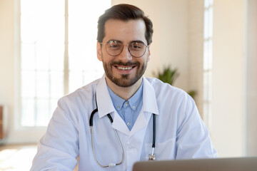 Head shot portrait smiling confident young doctor wearing glasses and medical uniform with...