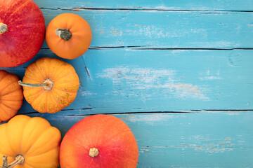Different sorts of orange Pumpkins, blue wooden background