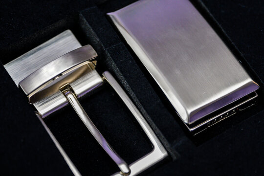 Shiny metal buckle and leather belt in a gift set.