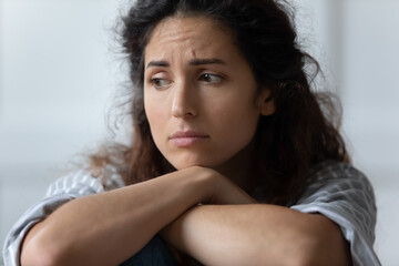 Close up sad woman sit indoor feels offended by beloved man. Female thinking about loneliness and...