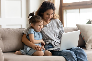 Happy mother with little daughter have fun online with new cool app, family watching cartoons, play...