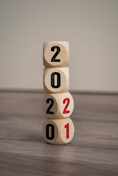 Tower made of cubes and dice with 2020 and 2021 on wooden background