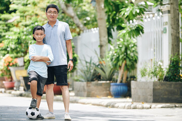 Smiling father posing with his preteen son after they played soccer together in the street