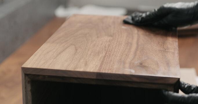 woodworker applying oil finish to black walnut storage box
