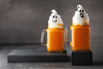 Halloween Pumpkin  cocktail with whipped cream in ghost shape. Freakshake for party.