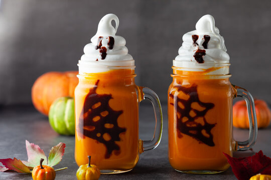 Halloween Pumpkin  cocktail with whipped cream in ghost shape and chocolate spider web. Freakshake for party.
