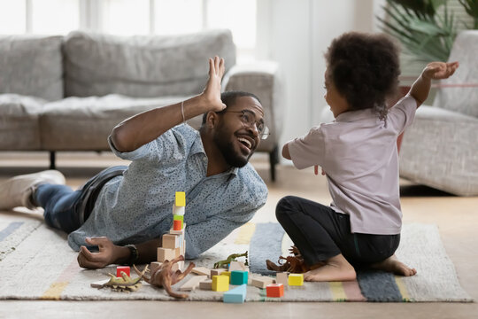 Happy young handsome biracial father lying on floor carpet, giving high five to joyful little preschool child son, finishing constructing building, cheerful multiracial family having fun on weekend.