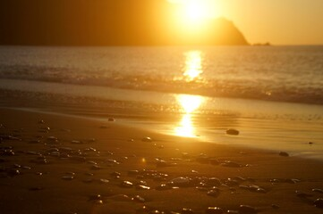 the sunrise is reflected on the smooth surface of the sea and wet stones