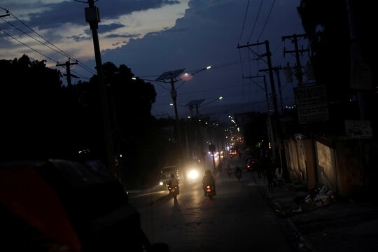 Vehicles drive along Delmas road at dusk in Port-au-Prince