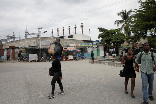 People walk along a street, with an electric power plant in the background, in Port-au-Prince