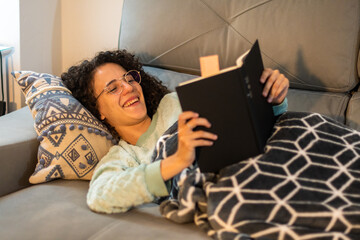 Stock photo of a beautiful and smiling young woman with curly hair and glasses reading a book at home, sitting on the coach. Curly girl with soft blanket and winter pajama reading and laughing.