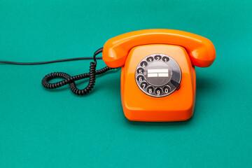 Retro phone orange color, vintage handset receiver on green background.