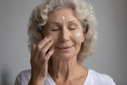Close up satisfied middle aged woman applying moisturizing face cream or lotion, happy positive mature senior female enjoying skincare procedure with closed eyes, anti aging cosmetic product