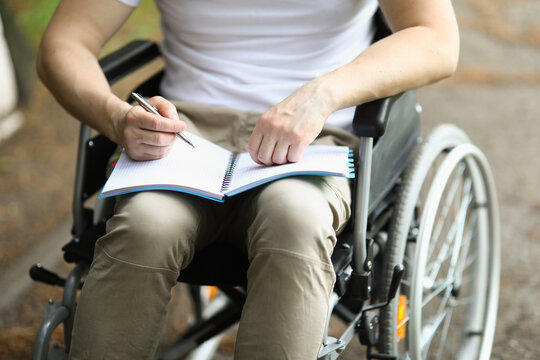 Man in wheelchair sits and holds notebook and pen. Learning professions of people with disabilities concept