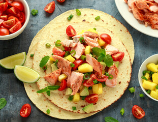 Salmon fish tacos with mango, avocado, tomato, spring onion and lime. Mexican food