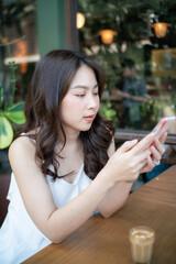 Business asian women use samrtphone sitting in coffee shop