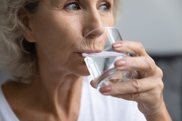 Close up thirsty beautiful middle aged woman drinking fresh pure mineral water, satisfied senior...