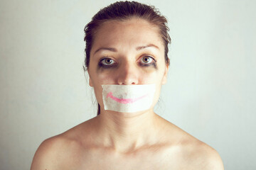 Unhappy woman with wrapping her mouth by adhesive tape painted smile