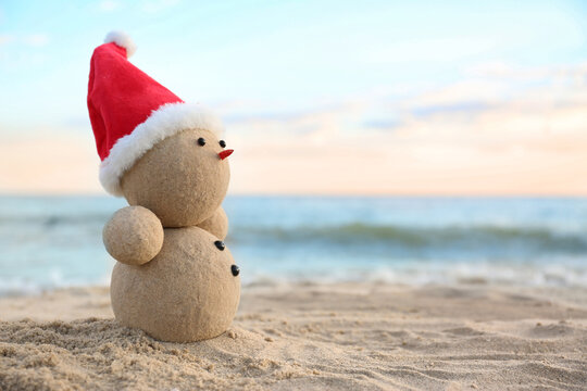 Snowman made of sand with Santa hat on beach near sea, space for text. Christmas vacation
