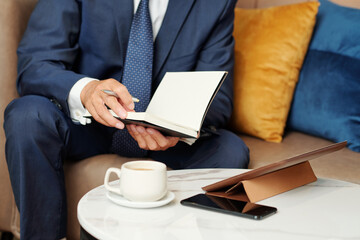 Cropped image of businessman checking planner before having online meeting with colleagues or business partner