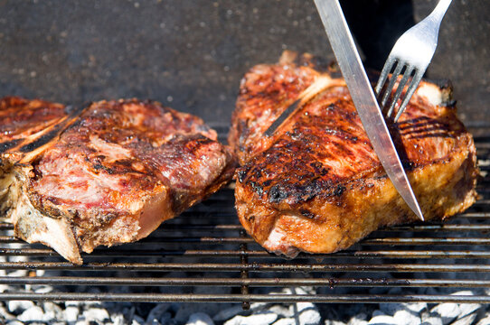 Barbeque, t-bone while cooking on the wood and charcoal grill