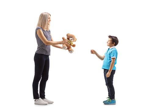 Full length profile shot of a woman giving a teddy bear to a boy