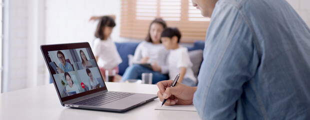 Fototapeta Asian business man stay with family and work remotely at home video conference remote call to corporate group. Meeting online,videocall, group discuss online concept. obraz