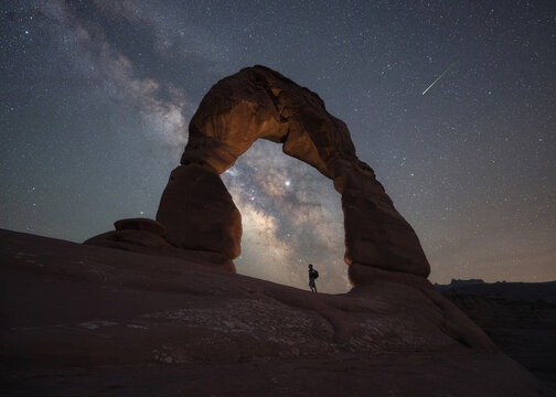 Hiker standing under Delicate Arch and the Night Sky