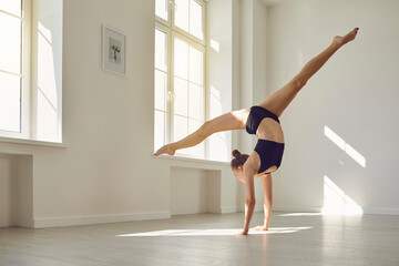 Slender gymnast in sports bra top and shorts doing handstand while practicing gymnastics in studio