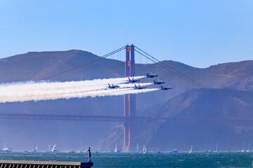 United States Navy Blue Angels aerobatic team's F-18 Hornet combat jets in flight over Golden Gate Bridge, San Francisco