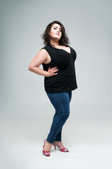 Plus size fashion model in black blouse and blue jeans, fat woman on gray background, body positive concept