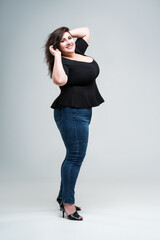 Happy plus size fashion model in black blouse and blue jeans, fat woman on gray background, body positive concept