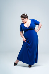 Plus size fashion model in blue dress with deep neckline, fat woman on gray background, body positive concept