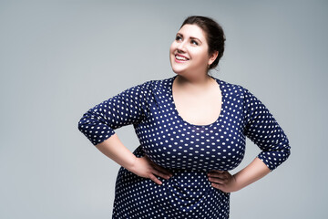 Happy plus size fashion model in blue polka dot dress, fat woman on gray background, body positive concept