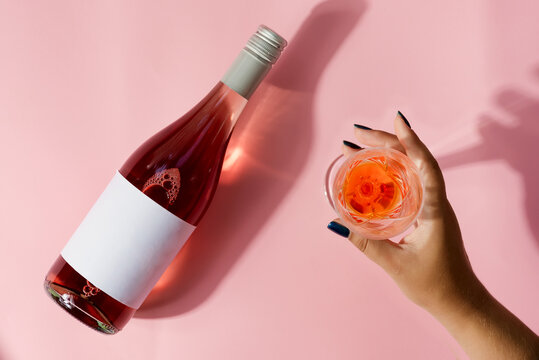 Woman's hand with a glass of rose wine and with rose wine mockup