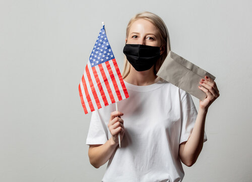 Blonde girl in face mask with USA flag and money on white background
