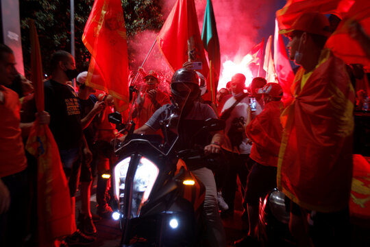 Man rides a motorbike though the crowd during post-election patriotic rally in Podgorica