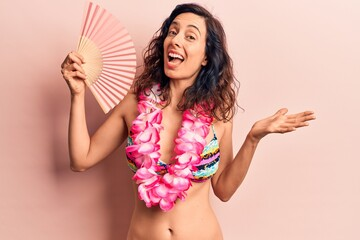 Young beautiful hispanic woman wearing bikini and hawaiian lei holding hand fan celebrating achievement with happy smile and winner expression with raised hand