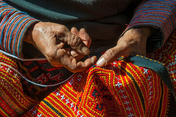 Hands of a Black Hmong woman sewing colorful traditional fabric and other arts and crafts with her hands in the sunlight, North Vietnam. Wall mural